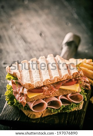 Healthy grilled ham, cheese and salad sandwich in double-decker form on toasted white bread served on an old wooden board on a rustic wooden table with copyspace - stock photo