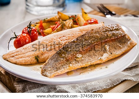 Healthy grilled or oven-baked fresh salmon fillets rich in omega-3 served with assorted roasted vegetables on a white plate for a tasty seafood dinner - stock photo