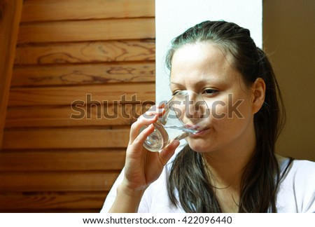 Healthy habits - pretty young woman drinking the glass of water - stock photo