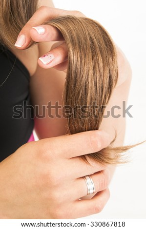 healthy Hair Growth concept. Portrait of beautiful young woman holding her long hair on white background - stock photo