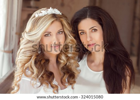 Healthy hair. Two beautiful girls. Brunette stylist and smiling blond girl bride with long curly hairstyle and bridal makeup. Wedding indoor portrait. - stock photo