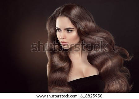 Healthy hair. Wavy hairstyle. Beautiful brunette woman model with clean skin advertising shiny brown straight long hair isolated on brown dark background.