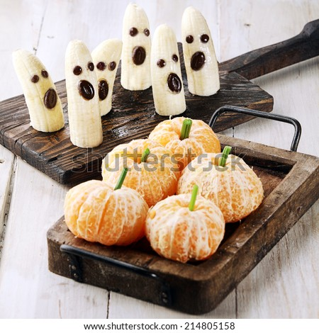 Healthy Halloween Treats Made into Banana Ghosts and Clementine Orange Pumpkins - stock photo
