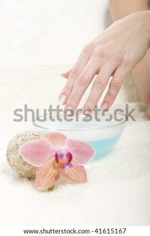 Healthy hands and professional wet french manicure on treated nails. orchid flower on white towel and water bowl as decoration