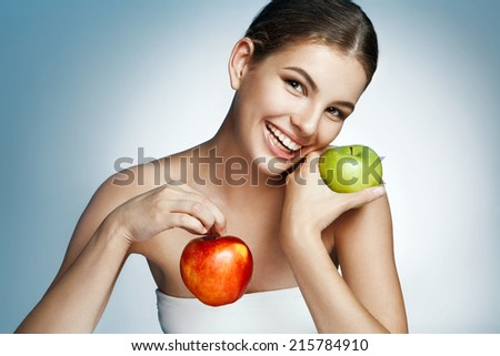 Healthy & Happy, natural organic raw fresh food concept / portrait of attractive girl of the holding two apples in her hands over blue background  - stock photo
