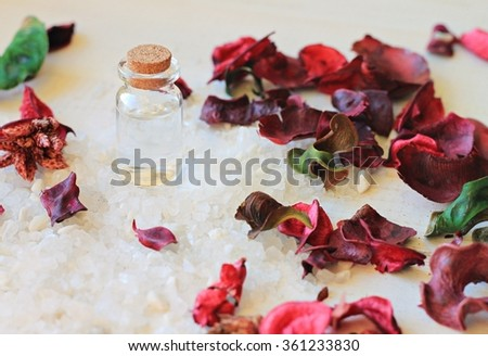 Healthy herbal salt cosmetic toiletries- bottle with essential oil, aromatic flowers, sea salt. Spa background - stock photo