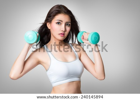 Healthy hispanic young asian woman with dumbbells working out, Isolated on grey background, Fitness gym concept - stock photo