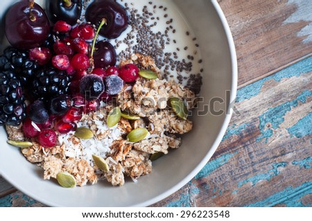 Healthy home made oatmeal porridge muesli with kefir yogurt and topped with blackberries, cherries,pomegranate, pumpkin and chia seeds. Served on a rustic wooden table. - stock photo