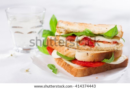 Healthy homemade caprese sandwich with tomato, mozzarella and basil, selective focus