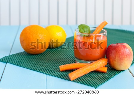 Healthy homemade carrot juice in glass and fresh carrot, apple, orange, lemon, spinach on light wooden background. Weight loss, healthy food, diet and detoxification - stock photo