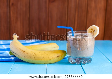 Healthy homemade Chocolate banana smoothie in glass and fresh bananas on wooden background. Weight loss, healthy food, diet and detoxification - stock photo