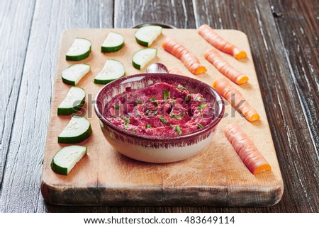 Healthy Homemade Creamy Hummus with beetroot in bowl surrounded by carrots and cucumber - vegan food