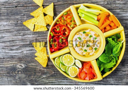Healthy homemade delicious spicy hummus with baby carrots, celery sticks, spinach, ginger, pepper and chilli, sliced lime, virgin olive oil, pine nuts and corn nachos, view from above - stock photo