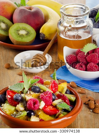 Healthy homemade fruit salad, fresh berries and fruits on   old wooden table. Top view