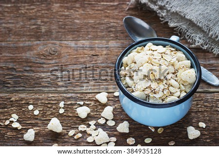 Healthy homemade granola or muesli with oats a metal mug the old dark wooden background retro - stock photo