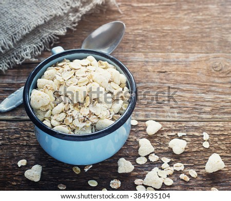 Healthy homemade granola or muesli with oats a metal mug the old dark wooden background retro toning - stock photo