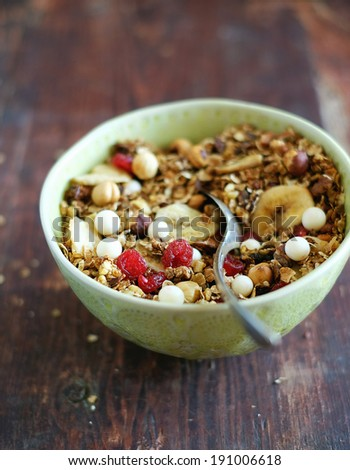 Healthy homemade granola or muesli with toasted oats, dried cherry, cranberry, figs, raisin, hazelnuts, cashew, walnuts, yogurt and white chocolate chips and honey in a bowl for breakfast or snack - stock photo