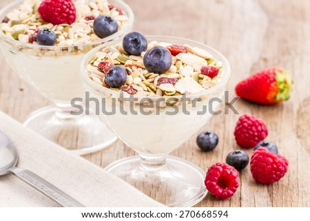 healthy homemade granola or muesli with toasted oats, dried cherry, cranberry, figs, raisin, hazelnuts, cashew, walnuts, yogurt and fresh fruits  - stock photo
