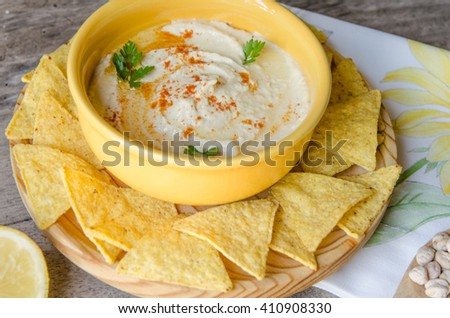 Healthy homemade hummus with olive oil and corn chips, on wood table.
