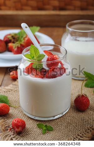 Healthy homemade yogurt in glass jar and fresh strawberries on wooden table - stock photo