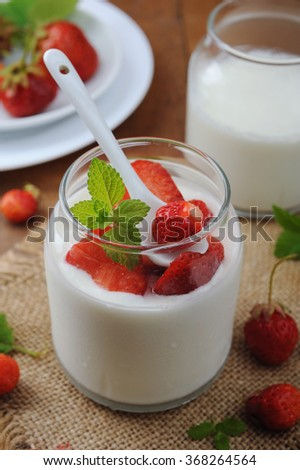 Healthy homemade yogurt in glass jar and fresh strawberries on wooden table