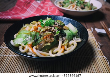 Healthy Japanese dish on wooden table; Vegetarian Udon Yaki. Udon stir fried with Bok choy, carrot, onion and champignons in garlic, ginger and soy sauce.