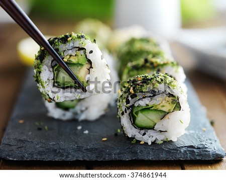 healthy kale and avocado sushi roll with chopsticks - stock photo