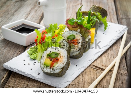 healthy kale and avocado sushi roll with chopsticks. Vegetarian rolls