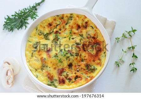 Healthy kale and bacon frittata with mushrooms and thyme makes a light lunch or dinner - stock photo