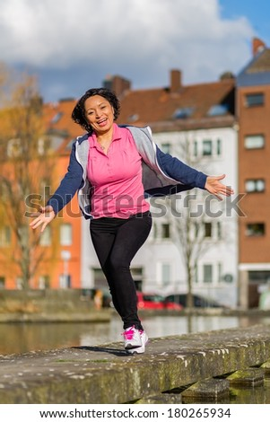 Healthy latina woman exercising in the city while jogging