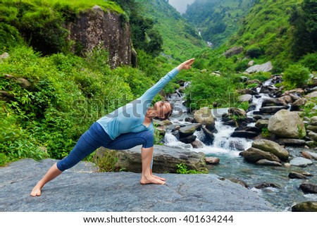 Healthy life exercise concept - Sporty fit woman practices yoga asana Utthita Parsvakonasana -  extended side angle pose outdoors at water