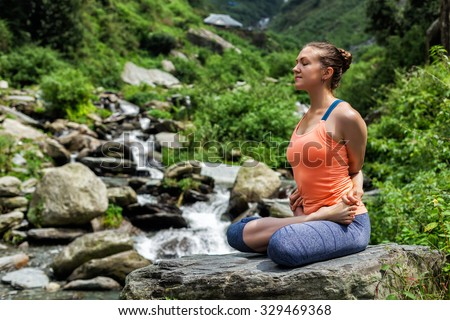 Healthy life exercise concept - Young sporty fit woman doing yoga - meditating in Baddha Padmasana (Bound Lotus Pose) asana outdoors at tropical waterfall