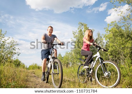Healthy life: sporty couple riding bicycles  in the forest - stock photo