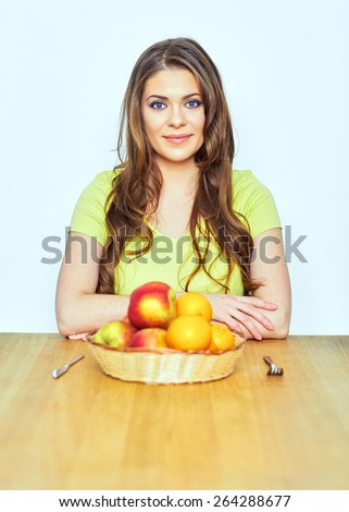 Healthy life style portrait of young woman with fruit sitting at the table. isolated.