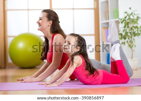 Healthy life. Woman and child girl exercising together