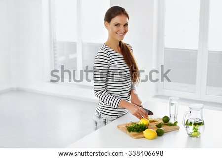 Healthy Lifestyle And Eating. Woman In The Kitchen Cutting Citrus Fruits, Lemons And Limes. Vitamin C. Detox Water. Lemonade. Diet. Dieting Concept. Healthy Food. Wellbeing, Wellness. - stock photo