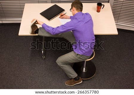 healthy lifestyle at work - business man writing on paper stretching leg sitting on pneumatic & The Painful Stool Stock Images Royalty-Free Images u0026 Vectors ... islam-shia.org