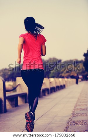 healthy lifestyle beautiful asian woman running at seaside under sunrise  - stock photo