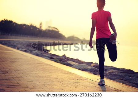 healthy lifestyle beautiful asian woman stretching legs before running at sunrise seaside  - stock photo