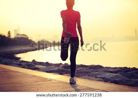 healthy lifestyle beautiful asian woman stretching legs before running at sunrise seaside