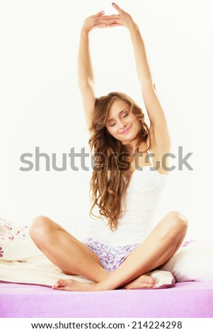 Healthy lifestyle. Cheerful happy woman teen girl waking up with a smile in bed and stretching her arms up - stock photo