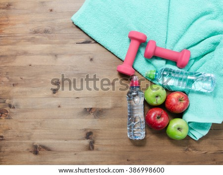 Healthy lifestyle concept. colored Apples dumbbells sport water bottles and turquoise towel on wooden table