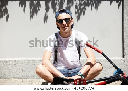 Healthy lifestyle concept. Teenager wearing glasses and snapback relaxing on the sidewalks during short break. Smiling young BMX rider sitting next to his bike on the sunny morning at the weekend - stock photo