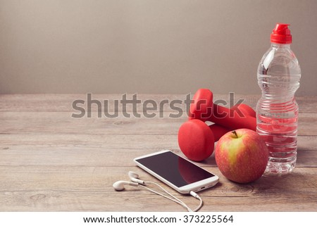 Healthy lifestyle concept with bottle of water, apple and smartphone on wooden background - stock photo