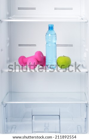 Healthy lifestyle, diet concept. Bottle of water, green apple and pink dumbbells  in empty refrigerator.  - stock photo