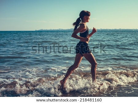 healthy lifestyle fitness girl jogging at sunrise/sunset beach  - stock photo