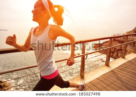 healthy lifestyle  fitness sports woman running on wooden trail seaside  - stock photo