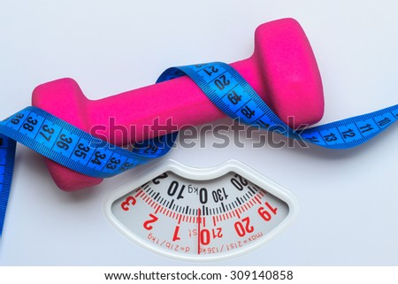 healthy lifestyle fitness weight control concept. Closeup pink dumbbell with blue measuring tape on white scales - stock photo