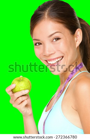 Healthy lifestyle. Fitness woman eating apple wearing measuring tape. Fit sporty multicultural Asian / Caucasian female fitness womanisolated cutout on green chroma key background. - stock photo