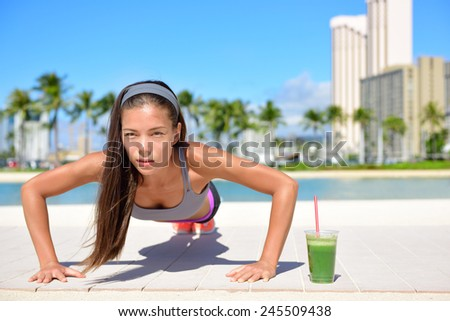 Healthy lifestyle fitness woman exercising drinking green vegetable smoothie doing push-ups training. Healthy female athlete working out doing exercise push ups on beach.  Asian Caucasian female girl. - stock photo